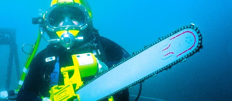 Commercial Diver Alan Strong with a chainsaw underwater